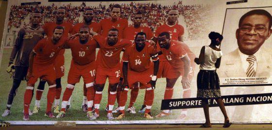 Una mujer mira un póster de la selección de fútbol de Guinea Ecuatorial junto al presidente Obiang.