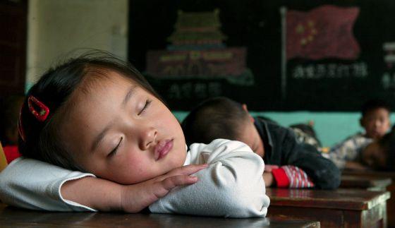 Varios alumnos duermen durante un descanso en un colegio en China.