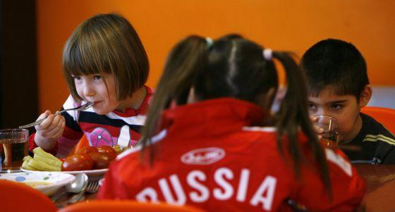 Niños huérfanos comen en el centro de menores donde viven en Rostov (Rusia).