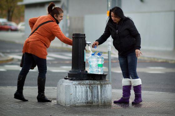 Dos vecinas de la corrala sevillana La utopía, que no tiene suministro, cogen agua en una fuente de la ciudad.