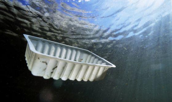 Un recipiente de plástico flota bajo el agua frente a la costa de Marsella.