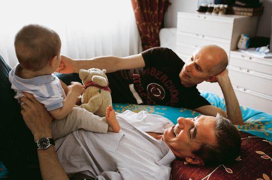Pedro Fuentes (con su hijo Alonso encima) y su marido Javier González, hace cuatro años.