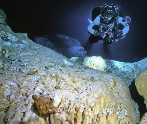 El buceador Alejando Álvarez inspeccionando el cráneo de Naia en la cueva de Yucatán.rn