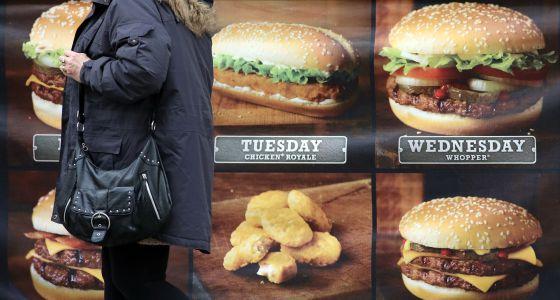 Una mujer, ante un anuncio de comida rápida.