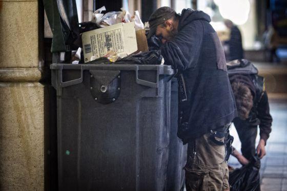 Un hombre busca en la basura, en las calles de Barcelona.