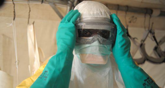 Un médico se coloca el traje de protección para entrar en la sala de aislamiento de Médicos Sin Fronteras en la región de Guekedou. rn  rn   rn  rn