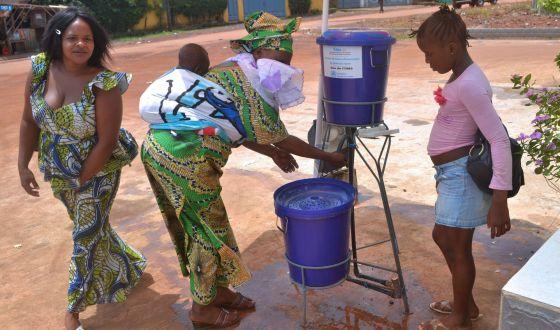 Un grupo de mujeres guineanas se lavan las manos en la entrada del hospital de Kipe.
