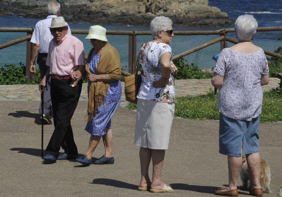 Personas mayores pasean cerca del mar en Tapia de Casariego (Asturias).
