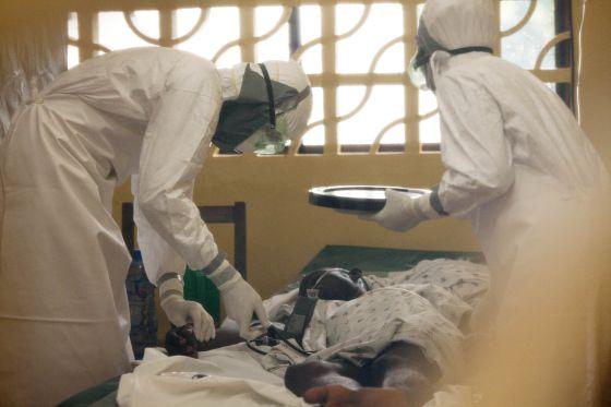 El doctor Brantly (izquierda) trata a un paciente de ébola.