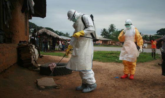 El personal sanitario desinfecta el entorno de una casa con un caso de ébola en Kailahun (Siera Leona).