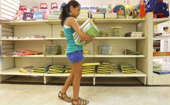Una niña recoge los libros de texto encargados en un centro comercial de la calle Preciados de Madrid.