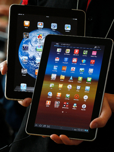 Un empleado surcoreano de la telefónica KT sostiene una tableta Samsung Galaxy junto a un iPad de Apple.