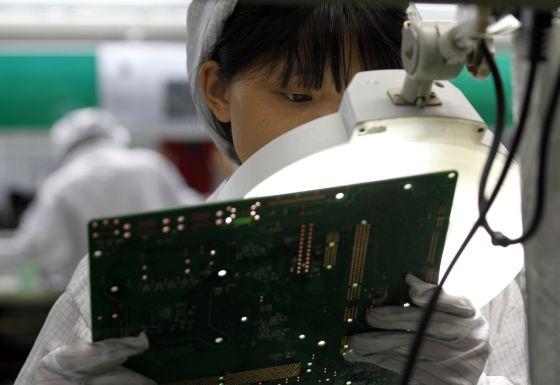 Una trabajadora de Foxconn maneja una placa