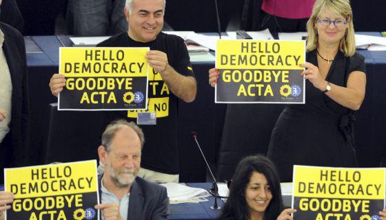 """Eurodiputados de Los Verdes muestran carteles con el mensaje """"Hola democracia. Adiós Acta""""."""