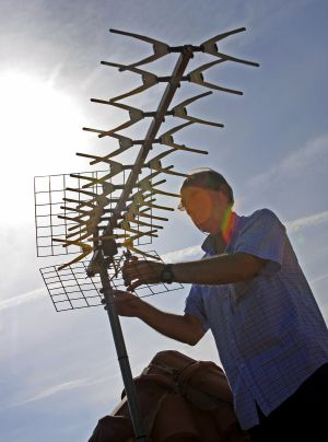 Un técnico instalando una antena de televisión.