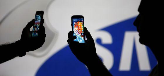Dos hombres con 'smartphones' en la mano.