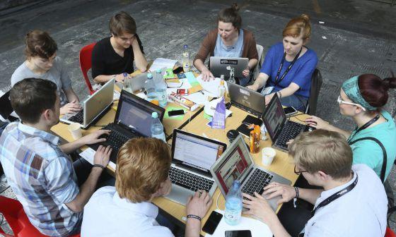 Varios jóvenes con sus ordenadores portátiles.