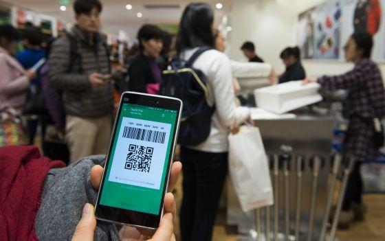 Una compradora muestra el código temporal generado por WeChat Pay en una tienda de la cadena japonesa Uniqlo en Shanghái.