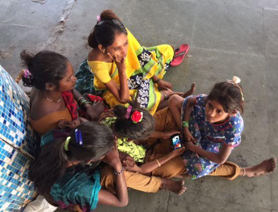 Un grupo de niñas se juntan al rededor de un teléfono en una estación de trenes de Bombay