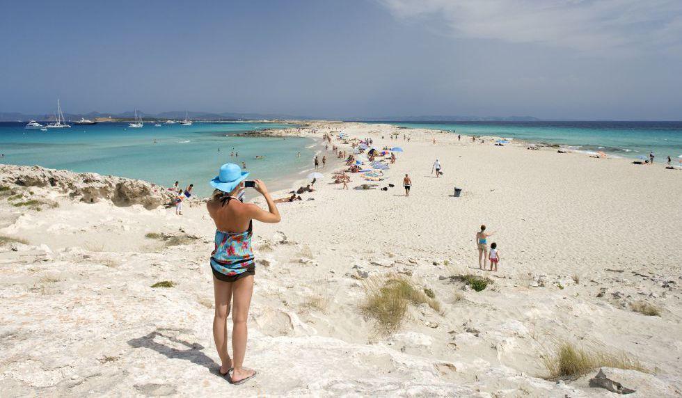 Una mujer fotografía la playa de Ses Illetes, en Formentera (Islas Baleares).