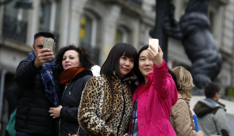 Turistas se hacen selfis en la Puerta del Sol de Madrid.