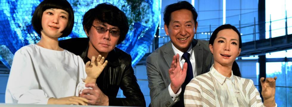Cientistas posam ao lado de robôs humanoides em Tóquio.