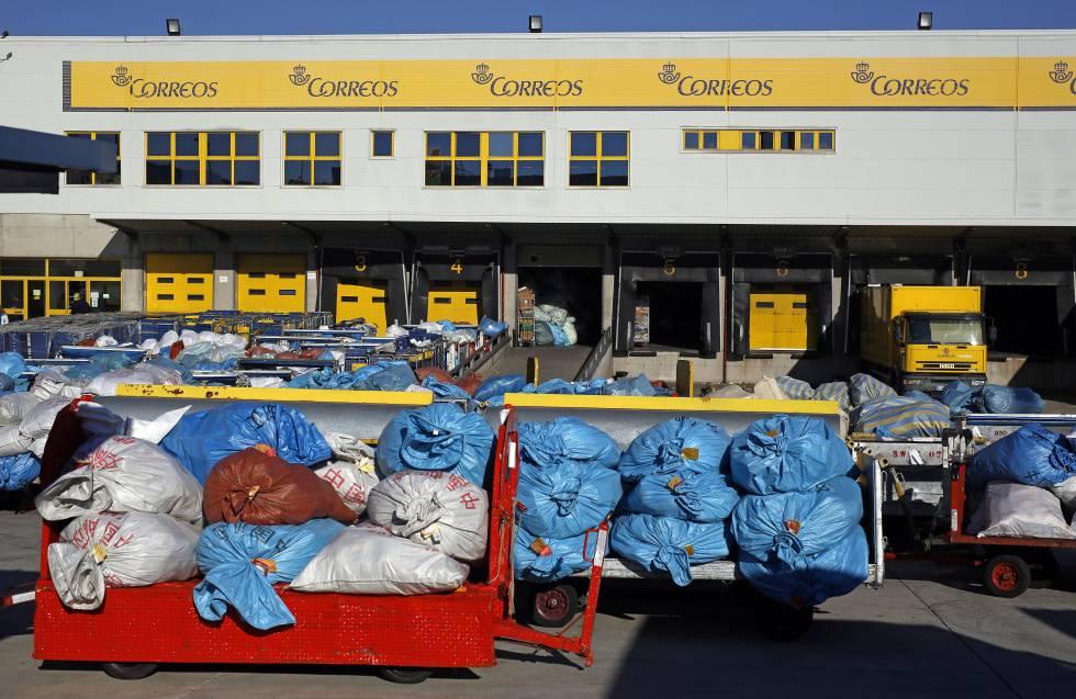 Decenas de sacas con envíos postales acumulados en el patio de las instalaciones de Correos en la terminal de carga del aeropuerto de Barajas, en Madrid.