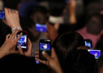 Un grupo de personas graba vídeos con sus móviles.