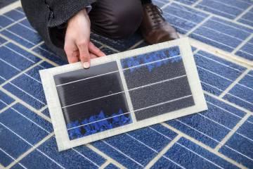 Un hombre muestra una parte de la carretera equipada con paneles solares durante su inauguración, en Tourouvre au Perche, Francia.