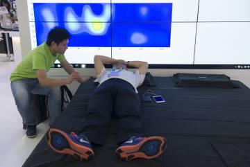 Un visitante prueba la cama inteligente de XSleep, que a través de multitud de sensores mantiene una posición correcta para dormir.