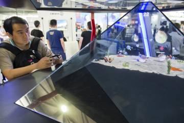 Un visitante juega con uno de los tres juegos diseñados por H+ Technology para su prototipo de videojuego holográfico.