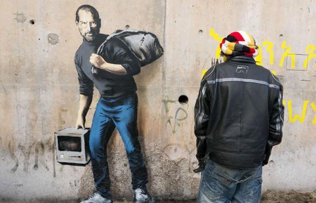 Un refugiado observa la última creación de Banksy con Steve Jobs como protagonista