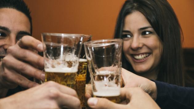 Un grupo de amigos brinda con cervezas en un bar