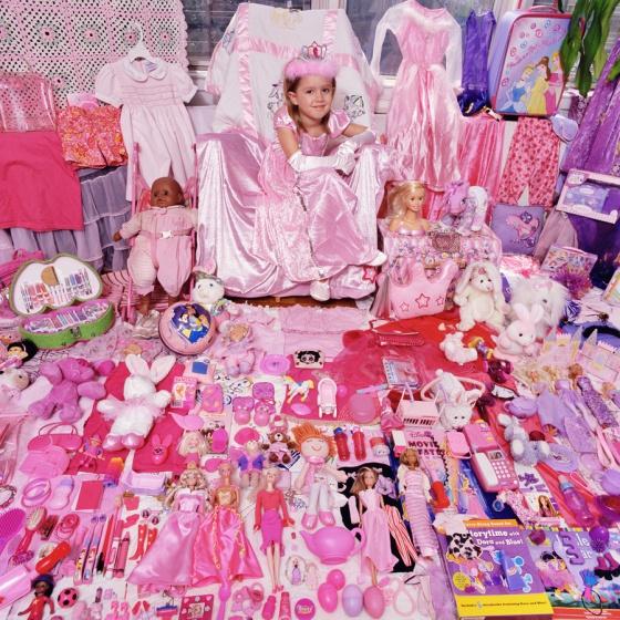 Menina mostra seus brinquedos cor-de-rosa.