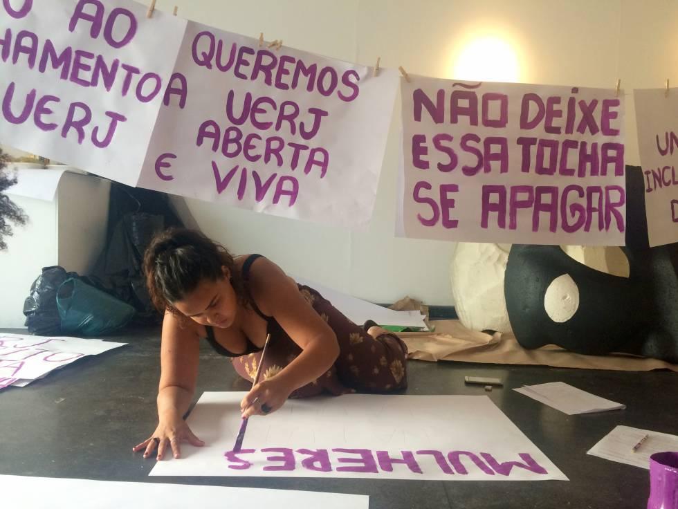 Aluna da UERJ confecciona cartazes de protesto na universidade.