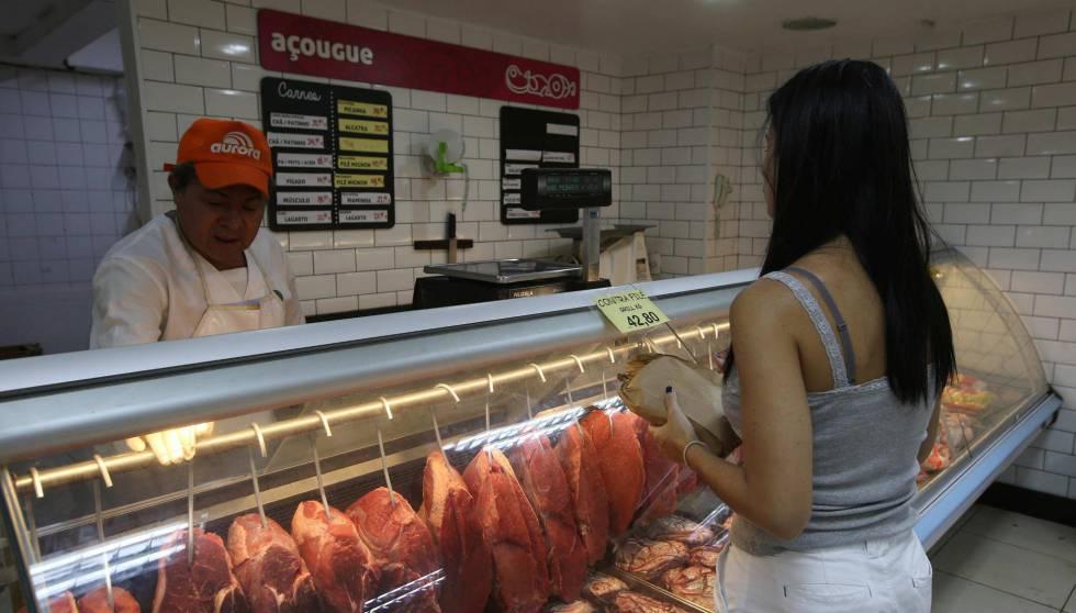 Mulher compra carne no Rio.