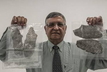 O professor Odorico Moraes segura duas embalagens com peles de tilápia prontas para o uso.
