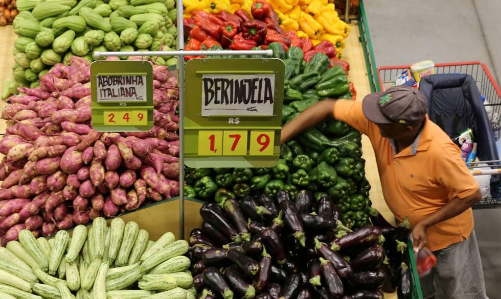 Consumidor escolhe legumes em um supermercado de São Paulo.