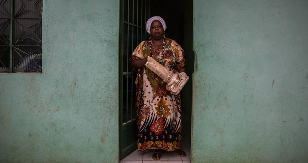 Madre Vivian en la puerta de la casa en Sepetiba con parte de la estructura de la casa de Seropédica en las manos.