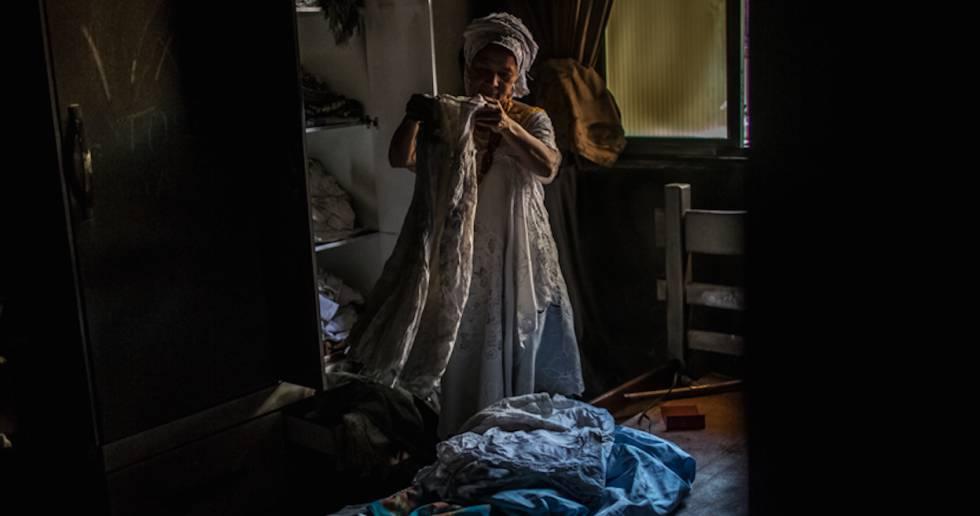 Madre Merinha mira las ropas de santo quemadas.