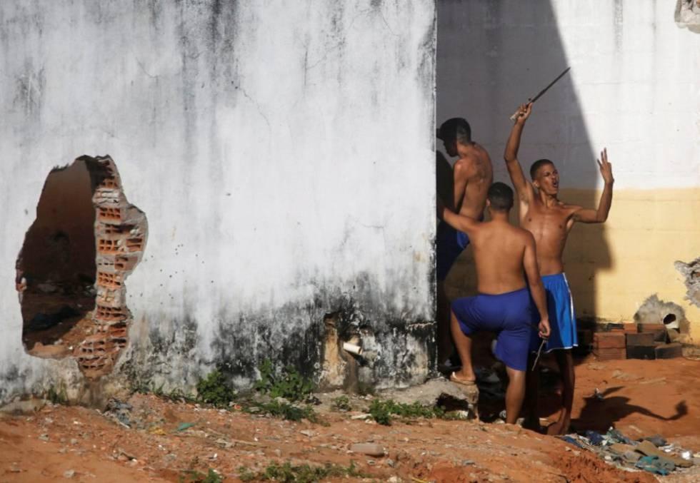 Detentos gesticulam para a polícia, que assiste de fora à movimentação em Alcaçuz em janeiro de 2017
