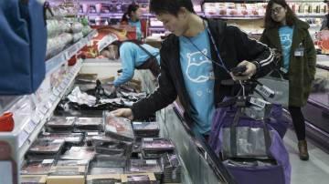 Funcionarios con camisetas azules circulan por la tienda recogiendo en bolsas las peticiones realizadas a través de la aplicación