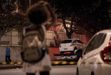 Moradora observa a polícia levar para a perícia o carro onde morreram Marielle Franco e Anderson Gomes na noite de quarta-feira.