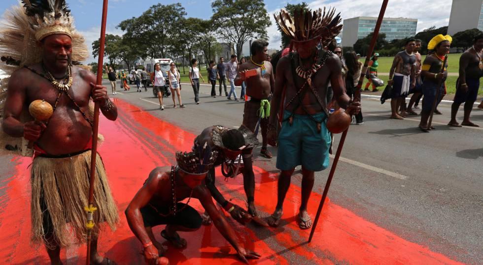 Índios pintam o chão para simbolizar o genocídio indígena no Brasil.
