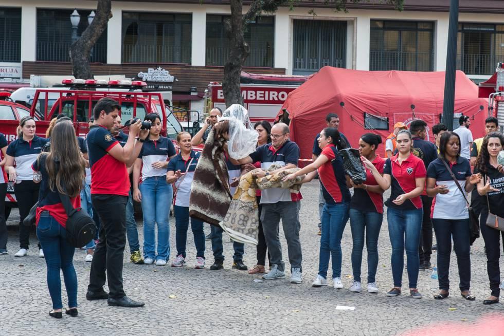 Voluntários da Igreja Universal fotografam a si mesmos enquanto doam aos desabrigados