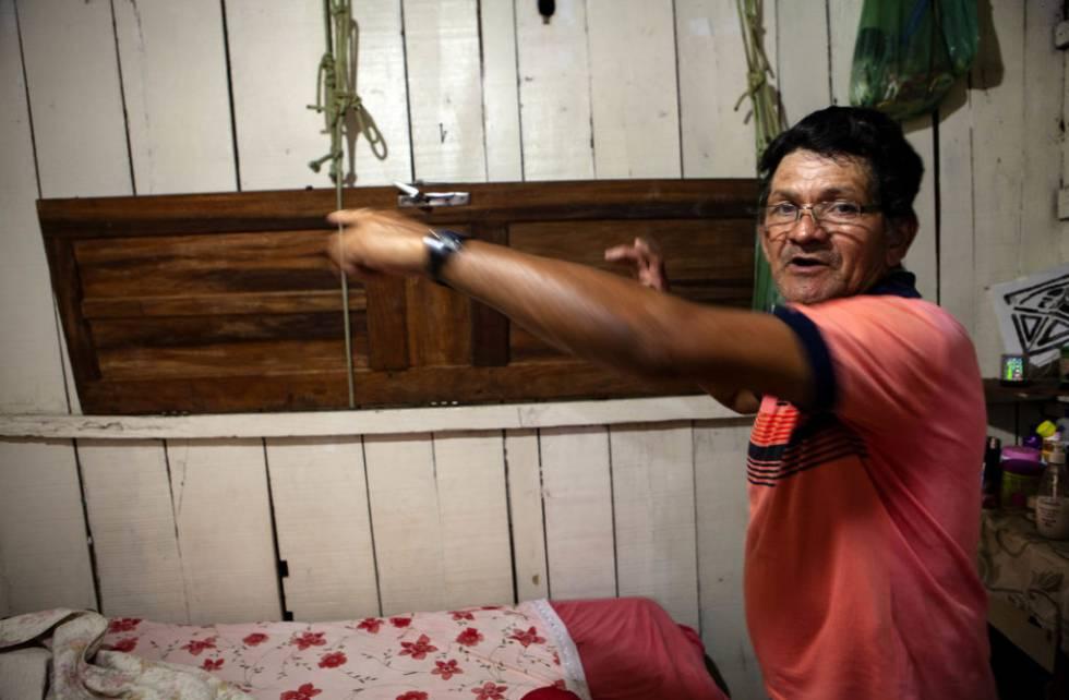 Carlos Alves Moraes, ribeirinho que virou pintor de paredes, mostra a porta suspensa por cordas que usa para erguer seus pertences mais importantes quando a casa alaga.