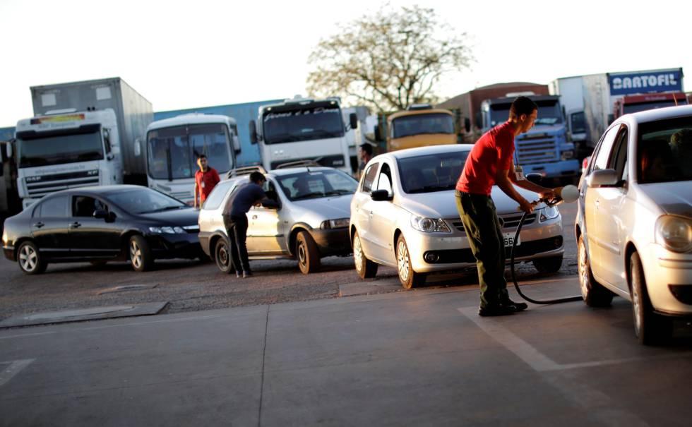 Frentista enche o tanque de carro em posto de combustível em Brasília.