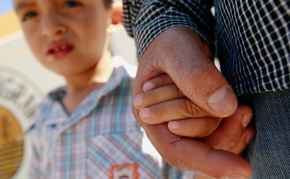 Imigrante salvadorenho Epigmenio Centeno segura a mão de seu filho, Steven.