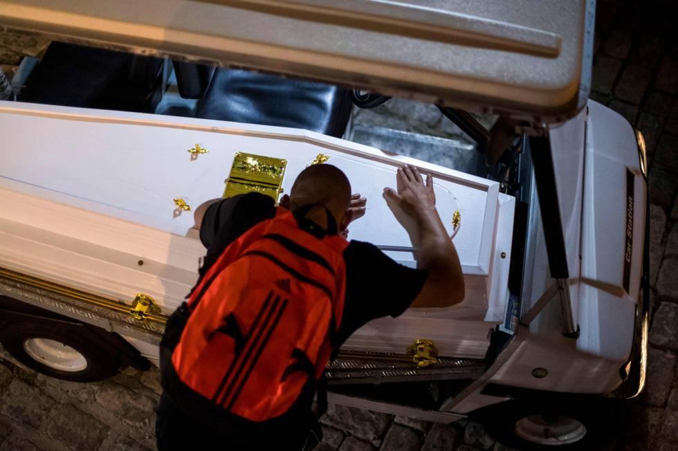 Pai de Marcos Vinícius chora sobre o caixão.
