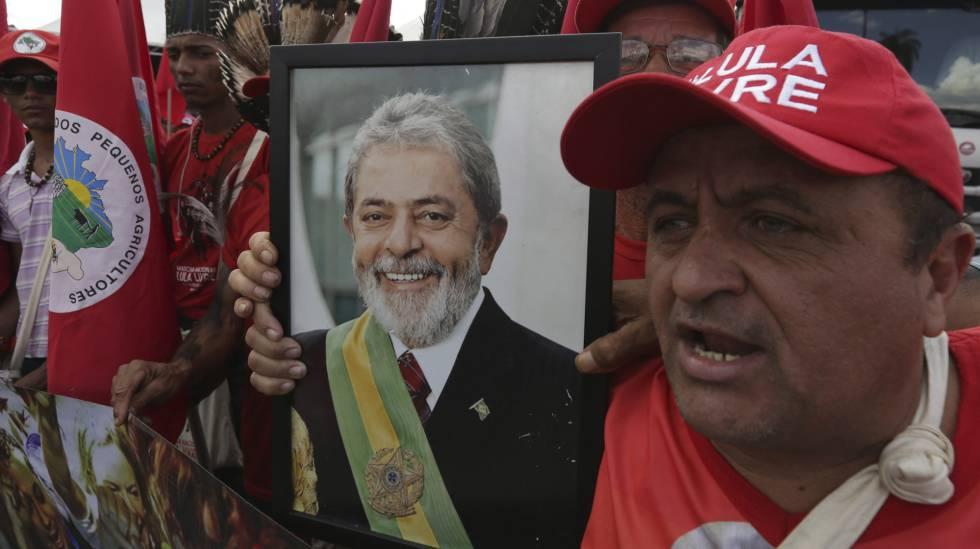 Militante do MST segura foto de Lula em protesto nesta quarta-feira, em Brasília.